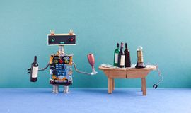 Funny robot gets drunk. Wine party celebration event concept. Creative design cyborg with wine glass and bottle. Wooden Stock Photo