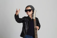 Funny rock child with guitar.little boy in sunglasses. Funny rock child with guitar.fashionable little boy in sunglasses.stylish kid in leather coat. music royalty free stock photos