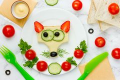 Funny sandwich for kids, animal shaped cheeseburger like a fox. With bread strawberry cheese cucumber olive stock photo