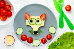 Funny sandwich for kids, animal shaped cheeseburger like a fox. With bread strawberry cheese cucumber olive royalty free stock image