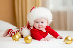 Funny Santa baby girl lying on bed Royalty Free Stock Images