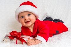 Funny Santa baby girl lying on white blanket with gift Stock Image