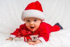 Funny Santa baby girl lying on white blanket with gift Stock Photo