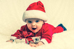 Funny Santa baby girl lying on white blanket with gift Royalty Free Stock Image