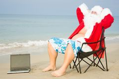 Funny Santa on the beach working on laptop. Sea, sun and vacation stock photography