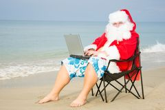 Funny Santa on the beach working on laptop. Sea, sun and vacation stock photos