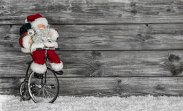 Funny Santa buying christmas presents decorated on wooden backgr Stock Photos