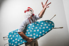 Funny santa claus babbo natale ironing surfer. On white background Royalty Free Stock Images