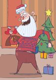 Funny Santa Claus in deer sweater smiling and dancing in decorated room with Christmas tree, stockings and fireplace Royalty Free Stock Photo