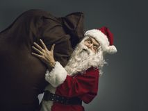 Santa Claus carrying a sack with Christmas gifts stock image