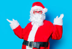 Funny Santa Claus have a fun with red eyeglasses. On blue background Royalty Free Stock Photos