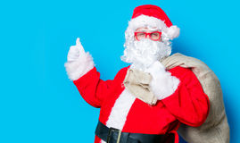 Funny Santa Claus have a fun with red eyeglasses. On blue background Stock Image