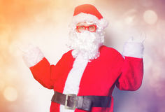 Funny Santa Claus have a fun with red eyeglasses. On blue background Royalty Free Stock Photography
