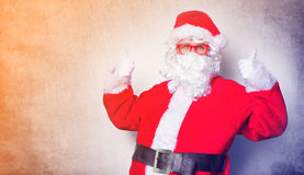 Funny Santa Claus have a fun with red eyeglasses. On blue background Stock Photography