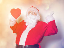 Santa Claus holding heart shape gift Royalty Free Stock Image