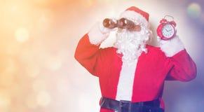 Santa Claus holding binoculars and alarm clock Royalty Free Stock Images