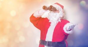 Funny Santa Claus holding binoculars Stock Photos