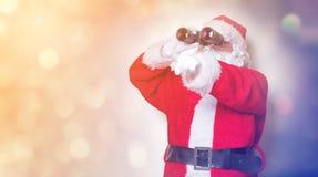 Funny Santa Claus holding binoculars Royalty Free Stock Images