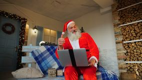 Funny Santa Claus showing thumbs up and working with laptop. Happy Father Christmas using approving gestures and enjoying with laptop. Cozy room with stock video