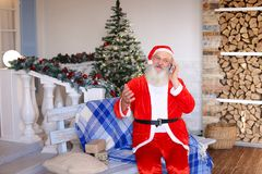 Hilarious Father Christmas calling parents by phone. Funny Santa Claus sitting in front of house and talking by phone.  Cheerful Father Christmas asking parents Royalty Free Stock Images