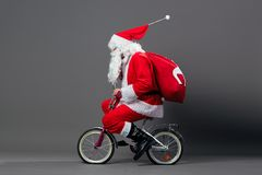 Funny Santa Claus in sunglasses and headphones with the bag with Christmas gifts on his back rides a bicycle on the stock photos