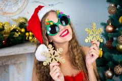 Funny santa girl. Beautiful woman holds gold snowflake, young lady female near big x-mas fir-tree tree, happy New Year party. Sexy santa girl, dreaming about Royalty Free Stock Photos