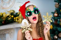 Funny santa girl. Beautiful woman holds gold snowflake, young lady female near big x-mas fir-tree tree, happy New Year party. Sexy santa girl, dreaming about Stock Images