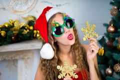 Funny santa girl. Beautiful woman holds gold snowflake, young lady female near big x-mas fir-tree tree, happy New Year party. Sexy santa girl, dreaming about Royalty Free Stock Images