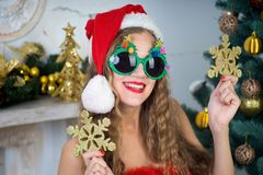 Funny santa girl. Beautiful woman holds gold snowflake, young lady female near big x-mas fir-tree tree, happy New Year party. Sexy santa girl, dreaming about Stock Image