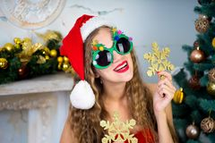 Funny santa girl. Beautiful woman holds gold snowflake, young lady female near big x-mas fir-tree tree, happy New Year party. Sexy santa girl, dreaming about Stock Photo