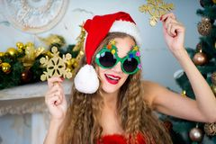 Funny santa girl. Beautiful woman holds gold snowflake, young lady female near big x-mas fir-tree tree, happy New Year party. Sexy santa girl, dreaming about Stock Photography