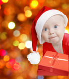 Funny santa present. Funny baby in Santa hat with present box on bright festive background, space for text Royalty Free Stock Images
