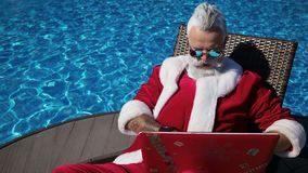 Funny Santa typing at laptop at summer holiday. Crazy funky Santa in sunglasses starting to work with mail before winter holiday. Comic emotional person open stock video