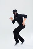 Funny scared criminal young man in balaclava running out Stock Image