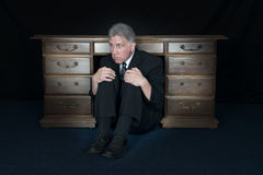 Funny Scared Fear Businessman Hide Under Office Desk. A fun and funny scared and fearful businessman hides under his desk. The man is having a bad day in his Royalty Free Stock Photos