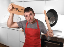Funny scared man holding pan wearing apron at kitchen asking for help Royalty Free Stock Image