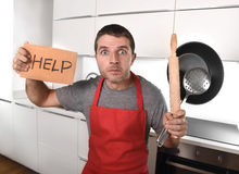 Funny scared man holding pan wearing apron at kitchen asking for help Royalty Free Stock Images