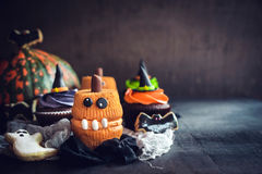 Scary Halloween cup cakes. Funny and scary Halloween cup cakes on wooden background with blank space Royalty Free Stock Images