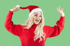 Beautiful blonde girl as a santa smiling to you. Funny scene of blonde, crazy woman wearing santa`s clothes Royalty Free Stock Photo