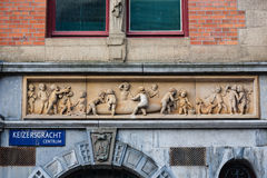 Funny scene of cigar elaboration. Haut-relief in Amsterdam street with a very funny group of children elaborating a cigar Stock Photos