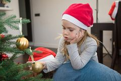Cute little girl with Santa hat and christmas ball resting on he Royalty Free Stock Photography
