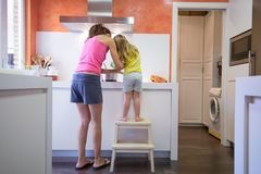 Mother and child cooking as a team. Funny scene. Woman mother and four years old blonde child on stool o ladder cooking together as a team, in electrical cooktop Stock Photography