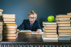Funny school boy reading a book at library. Joke!. Table with many books and one green apple. Child dressed in school uniform and glasses. Blackboard. Student Stock Image