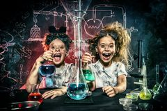 Funny little experimenters. Funny school children doing experiments in the laboratory. Explosion in the laboratory. Science and education royalty free stock images