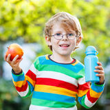 Funny school kid boy with books, apple and drink bottle. Funny little boy with apple and drink bottle on his first day to elementary school or nursery. Outdoors Royalty Free Stock Photo