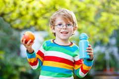 Funny school kid boy with books, apple and drink bottle. Funny little boy with apple and drink bottle on his first day to elementary school or nursery. Outdoors Royalty Free Stock Image
