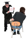 Funny School Teacher, Student Bad Failing Grade. A schoolteacher or college professor gives a school student a bad, failing grade. The young man is in trouble royalty free stock photos