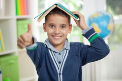 Funny schoolboy with a book on head Stock Photo