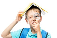 Funny schoolboy with book on head looking through magnifier Royalty Free Stock Image