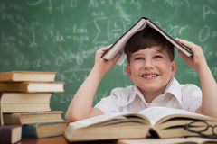 Funny schoolboy  holding book over head Stock Images